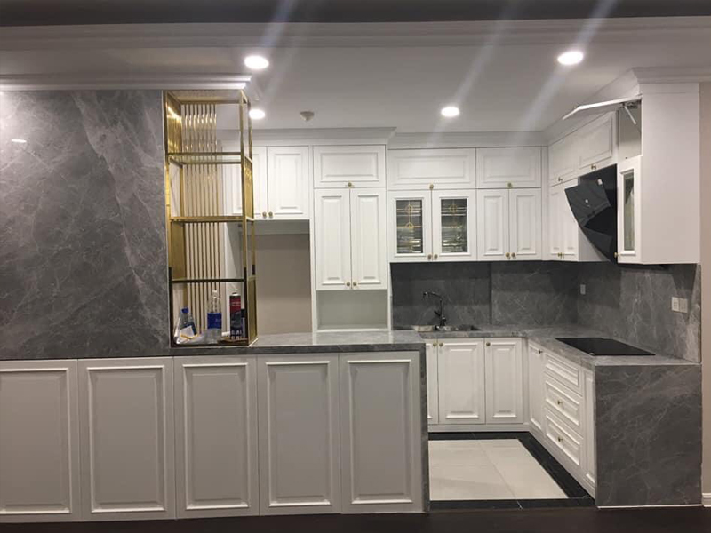 Mẫu tủ bếp tân cổ điển được sơn màu trắng sử dụng gỗ công nghiệp MDF lõi xanh chống ẩm có kết hợp bàn đảo độc lập
